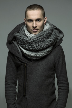 Young handsome man in a light grey wrap, shwal photo