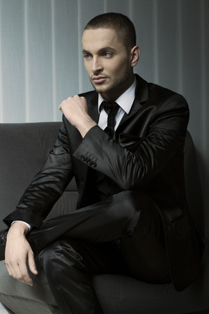 elegant young fashion man in tuxedo sitting on photo