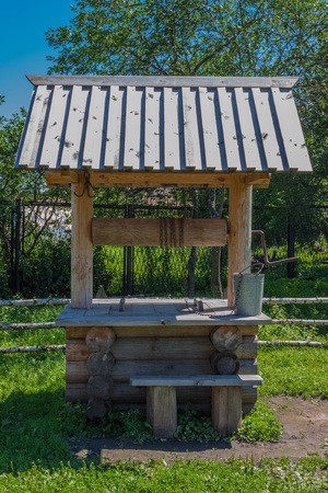 the medieval: Old village well with a wood roof with green garden on background Stock Photo