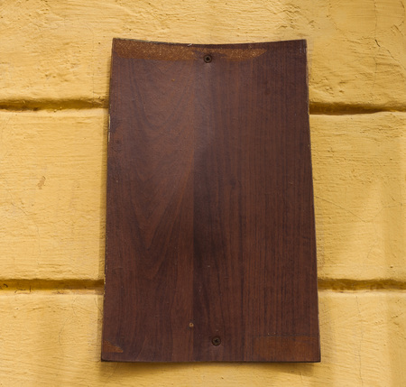 fake newspaper: Old wooden board hanging on the wall of a building