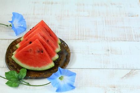 Watermelon slice arranged on a white wooden board