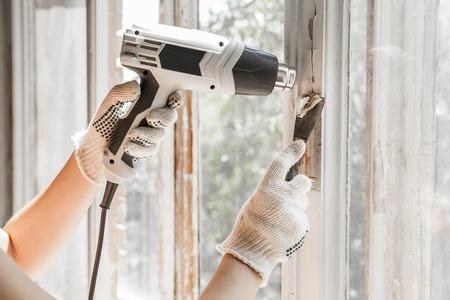 Master verwijdert oude verf uit raam met warmte pistool en schraper. Detailopname.