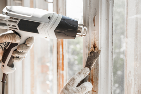scraper: Master removes old paint from window with heat gun and scraper. Closeup Stock Photo