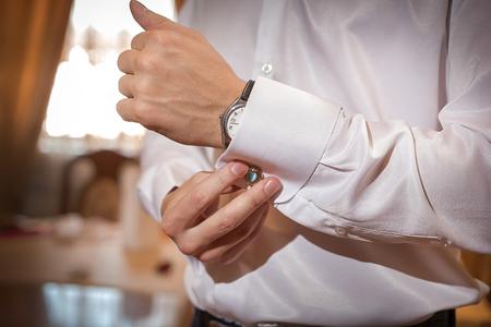 man fixes cufflinks on white shirt closeup Stock Photo