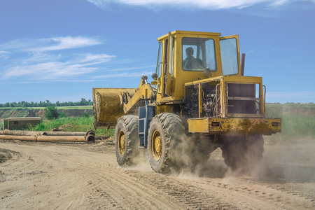 yellow bulldozer rides on the sand road.
