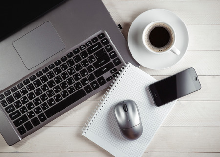 Cup of coffee and notebook, laptop, computer mouse, phone on a table.