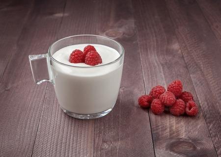 Raspberry on a table and in a glass of yogurt. 版權商用圖片