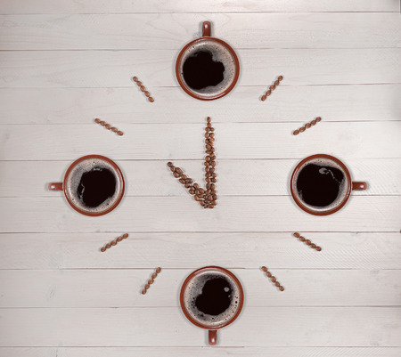 Clock made of coffee beans and cups on wooden background.