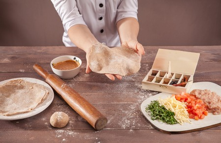women hands chef sculpts pastry for tacos on wooden table