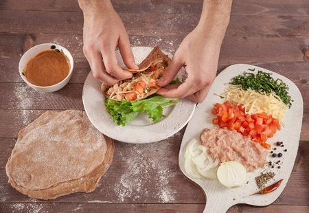 hands chef wrap tacos on wooden table top view
