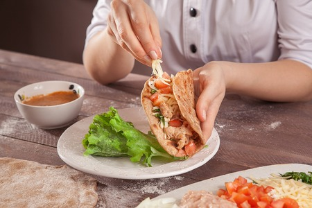 mexican ethnicity: Chef hands stuffed tacos on wooden table closeup