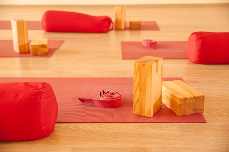 Group of yoga mat, wooden blocks, pillow and strap in class.