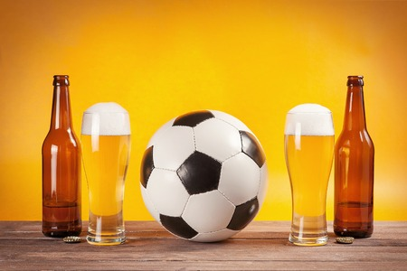 two glasses of beer and bottles near soccer ball on yellow background