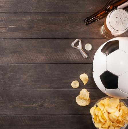 glas bier. snack en voetbal met kopie ruimte. Houten achtergrond