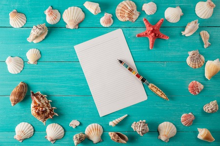 paper for notes near seashells on turquoise wooden background