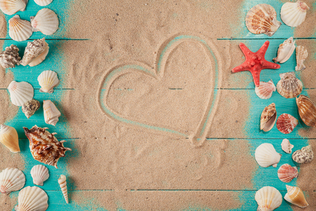 Heart drawing on sand among seashells. woden background