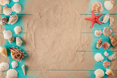 Frame of seashellson on sand wooden background. Space for text. 版權商用圖片