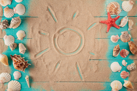 Sun drawing on sand among seashells. woden background 版權商用圖片