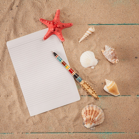paper for notes with pen near seashells on  sand background. copy space