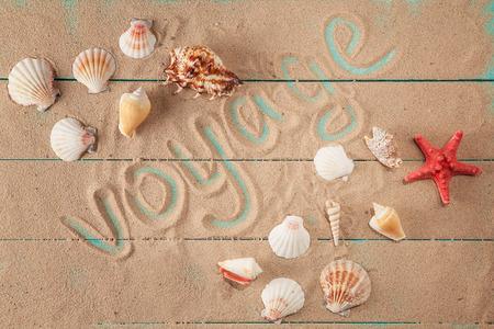 Word  voyage written on sand among seashells. woden background