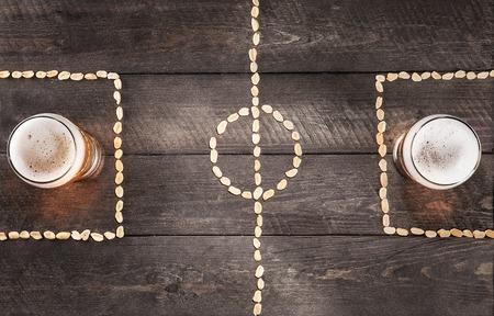 Twee glazen bier op een miniatuur voetbalveld markeringen van pinda's. bovenaanzicht