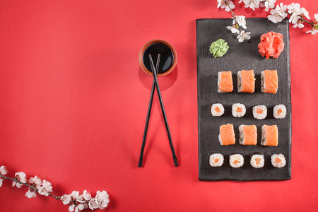 sushi roll on plate with chopsticks, ginger, soy, wasabi and sakura. Sushi at red table. Flat lay, top view. Copyspace