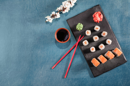 sushi roll on plate with chopsticks, ginger, soy, wasabi and sakura. Sushi at blue table. Flat lay, top view. Copyspace
