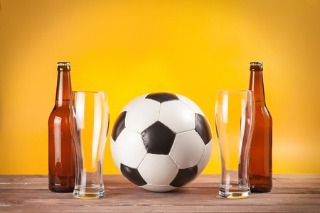two empty glasses of beer and bottles near soccer ball on wooden background