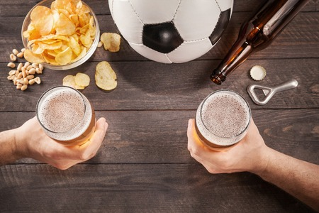 two glasses of beer in mens hands. Chin-chin. Top view