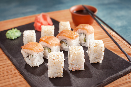 sushi roll on cooking plate with chopsticks, ginger, soy and wasabi. closeup. 版權商用圖片