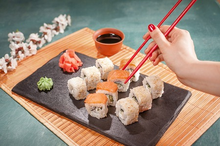 Hand with red chopsticks on sushi set with soy sauce, wasabi, sakura and ginger on black cooking desk
