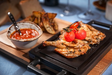 Grilled chicken with tomato sauce on iron plate. Closeup.