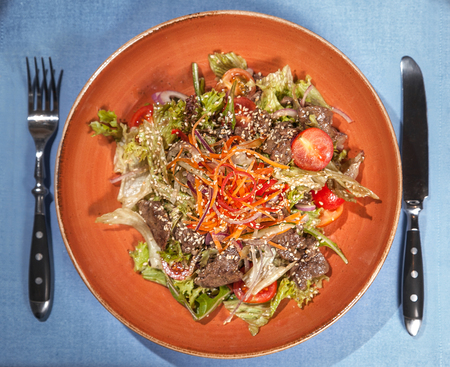 Salad leaves with sliced roast beef and cherry tomatoes on on blue table. With knife and fork 版權商用圖片