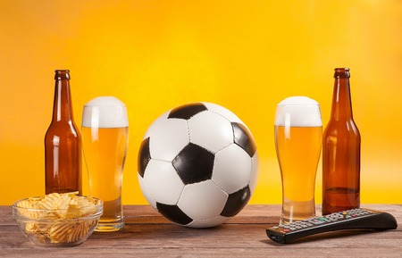 near beer: glass with beer and soccer ball near tv remote on wooden table. yellow background. snack in dish Stock Photo