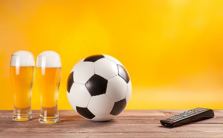 two glasses with beer and soccer ball near tv remote. Free space fro text. Yellow backround