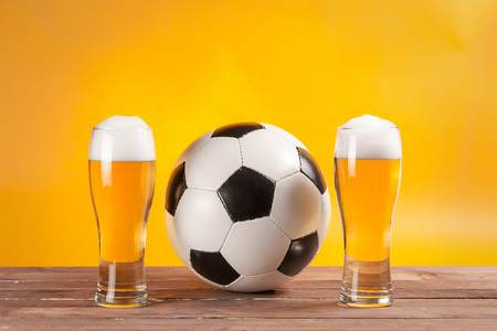 two glasses with beer and soccer ball near tv remote. Free space fro text
