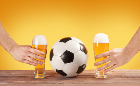 two male hands holding glasses of beer near soccer ball. Yealow background