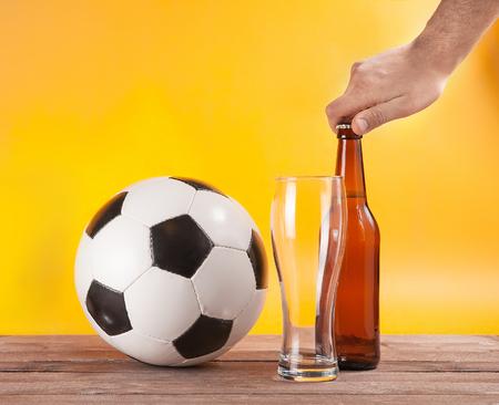 male hand open bottle of beer near soccer ball and empty glass 版權商用圖片