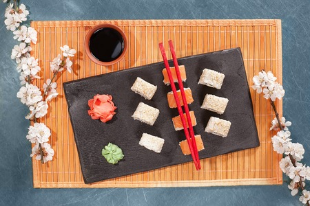 sushi roll on mat with chopsticks, ginger, soy, wasabi and sakura. Sushi at blue table. Flat lay, top view. Copyspace