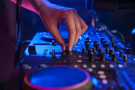 dj hand on mixing controller in blue light. closeup. 版權商用圖片