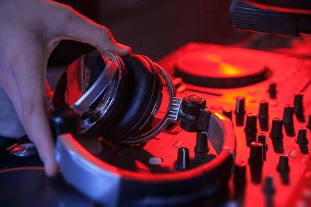 dj hand hold headphones near mixing controller in red light. closeup. 版權商用圖片