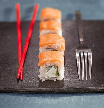 Chopsticks or fork. Chopsticks and fork with sushi on black plate. Closeup. Concept. Idea