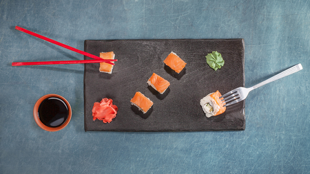 Chopsticks or fork. Chopsticks and fork with sushi on black plate. flat lay. top view. Concept. Idea