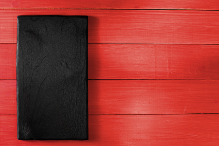 black cooking desk on red wooden table. Flat lay. Top view. Copy space for text. Design background.
