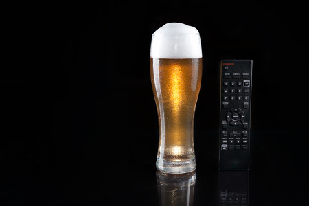 Glass of beer with TV remote on mirror. Dark luxury style. Design.