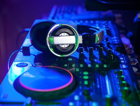 dj headpones on mixing controller in blue light. closeup.