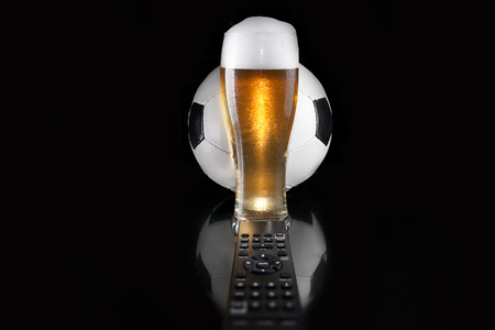 Soccer ball over glass of beer with TV remote on mirror. Dark luxury style. Design. 版權商用圖片