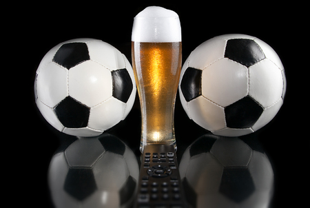 Glass of beer with TV remote between two soccer ball. Dark luxury style. Design.