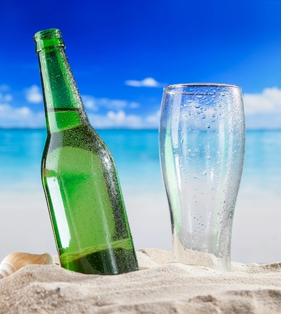 Bottle of beer with empty glass in sand at beach.