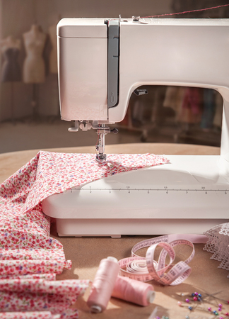 Closeup of needle sewing machine with pink tissue.